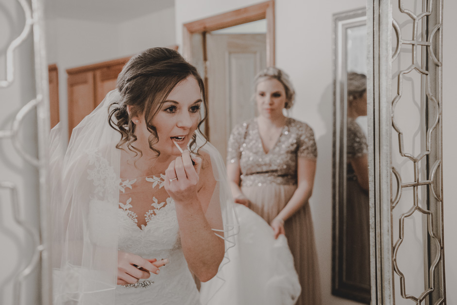bride applying make up in mirror with bridesmaid in background