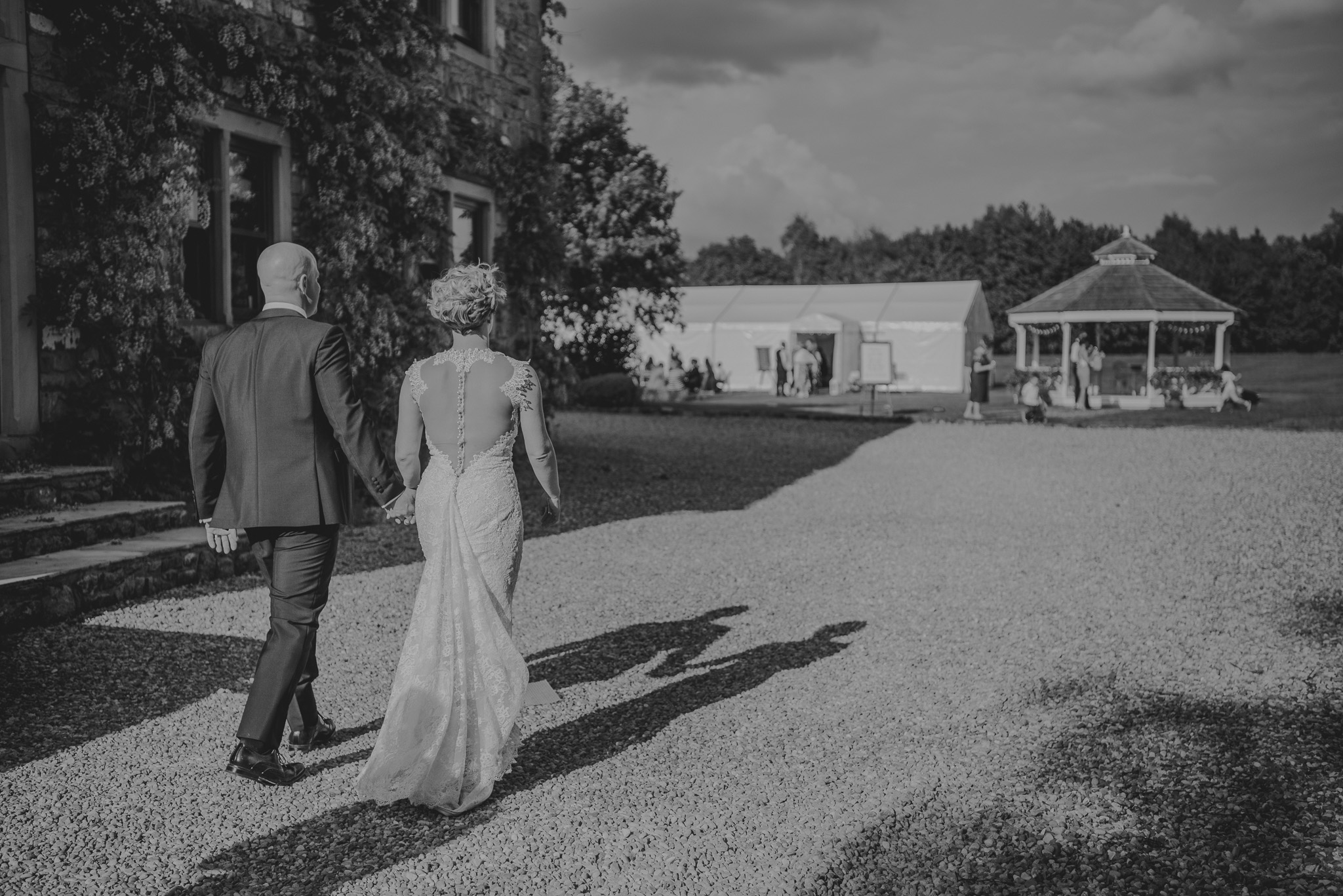 bride and groom walk back to marquee