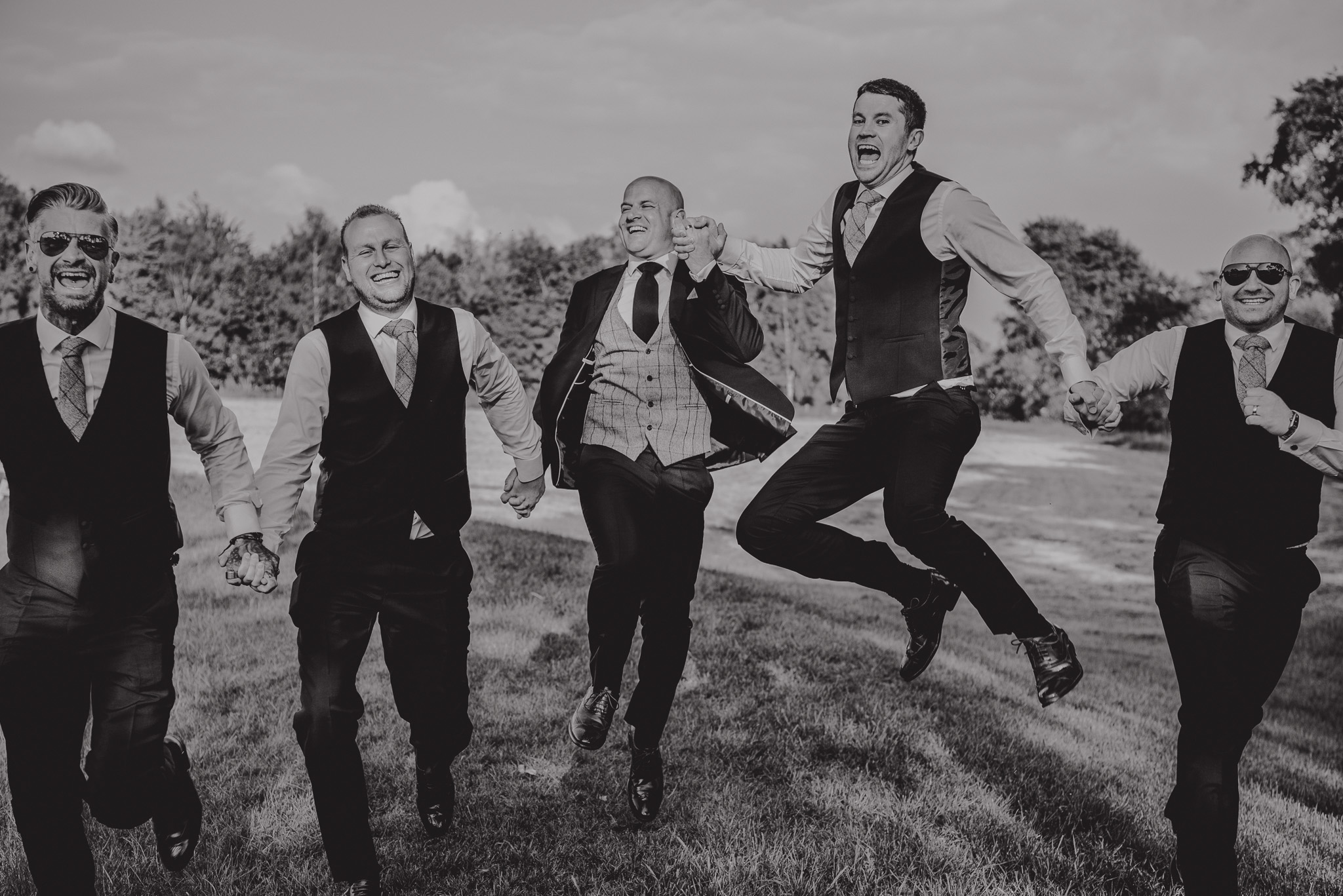 groomsmen jumping for picture