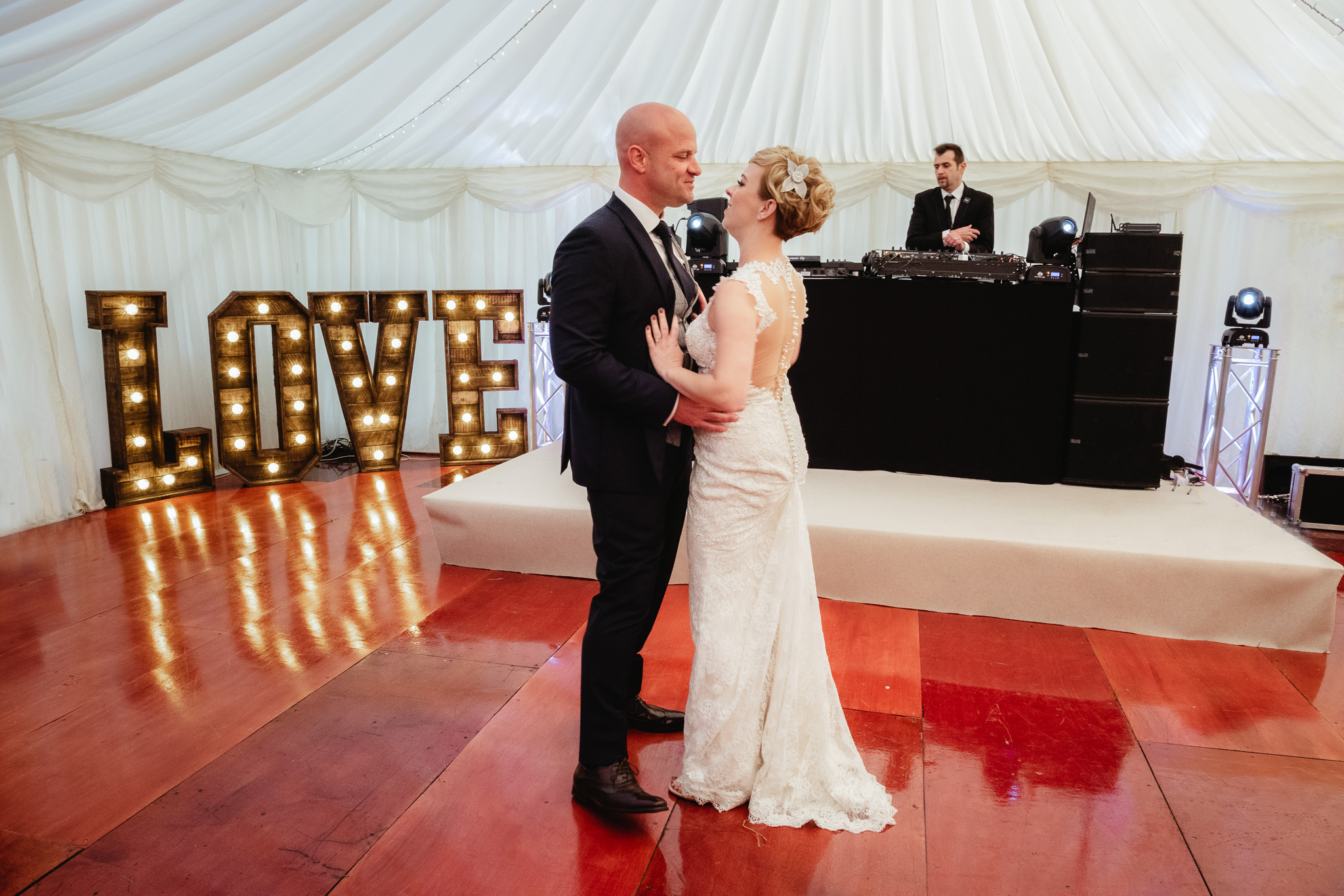 bride and groom starting first dance with love sign in background