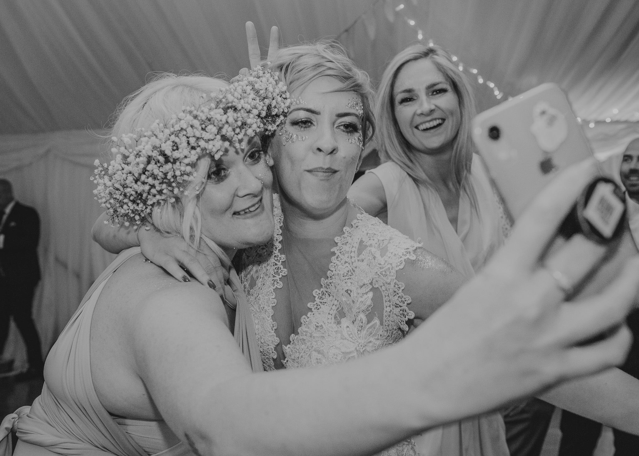 bride and bridesmaid selfie being photobombed